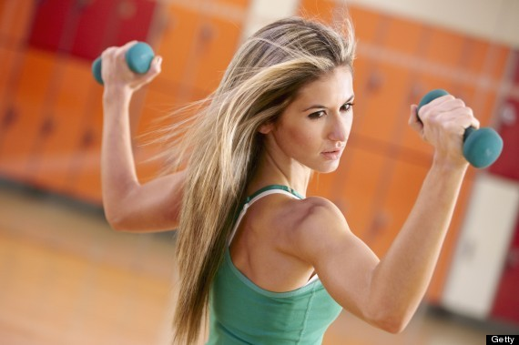 Young woman in gym doing exercise with dumbbells