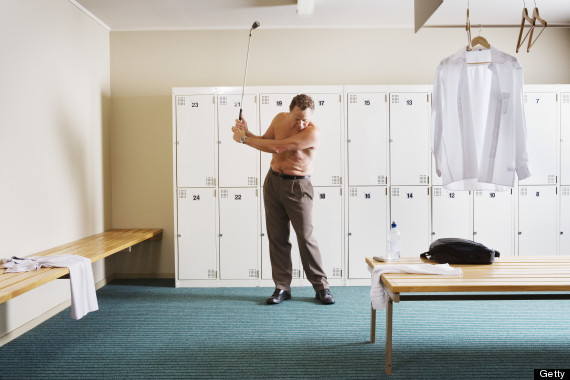 Bare chested mature man swinging golf club in locker room
